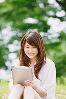 新緑とiPadを見る日本人女性
