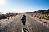 アメリカ 乾いた道路を歩く男性