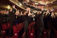 劇場でスタンディングオベーションする観客