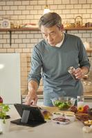 タブレットでレシピを見るシニアの日本人男性