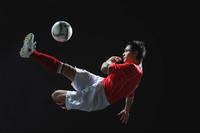 ボレーシュートをするサッカー選手
