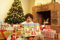 クリスマスプレゼントを覗いて喜ぶ男の子