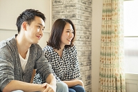 ソファーに座る若い日本人夫婦