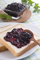 ブルーベリージャムをパンに塗る