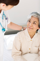 シニア女性患者と話をする看護師