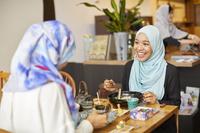 レストランで食事をするムスリムの女性