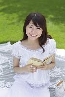芝生で読書をする若い日本人女性