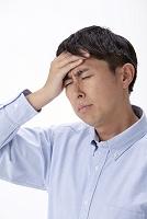 発熱で頭に手をやる日本人男性