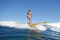 パドルサーフィンで波に乗る女性