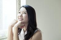 上を向いて微笑む20代日本人女性