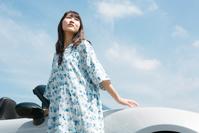 車のそばに立っている日本人女性