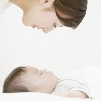 眠る赤ちゃんを見る母親