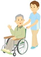 介護士に車いすを押してもらう老人男性