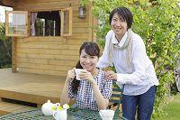 庭のテーブルでお茶を楽しむ若いカップル