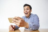 スマートフォンを見る日本人男性