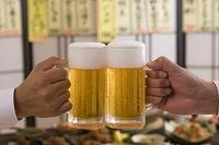 居酒屋でビールジョッキで乾杯する