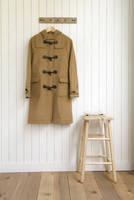 壁に掛けられたダッフルコートと椅子