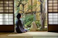 和室から庭を眺める女性