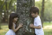 木を挟んで見つめ合うハーフの男の子と女の子