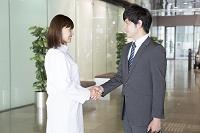 握手をするビジネスマンと女性医師