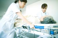 ストレッチャーに乗せた患者を運ぶ看護師