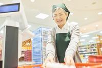 スーパーのレジで働く日本人のシニア女性