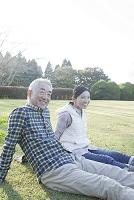 芝生の上でリラックスるシニア夫婦