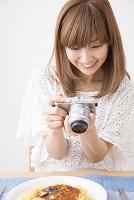 料理の写真を撮る日本人女性