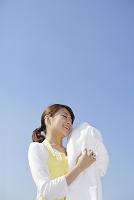 青空の下でまっ白なタオルを持つ日本人女性