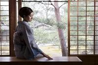 椅子に座って日本庭園を眺める着物の日本人女性