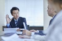 会議で説明をする日本人ビジネスマン