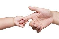 父の指を握る赤ちゃんの手