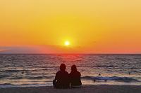 静岡県 伊豆白浜 浜辺に座るカップルと朝日