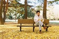 黄葉と読書する日本人男性