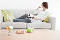 ソファーで本を読む日本人女性