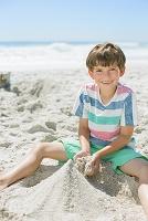 砂浜で砂遊びをする男の子