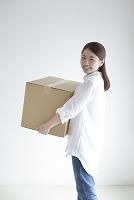 段ボール箱を持つ笑顔の日本人女性