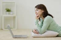 リビングで寛ぎながらパソコンをする女性