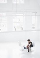 真っ白な部屋で働くビジネス女性