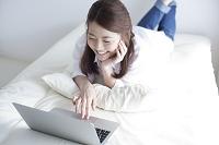 ベッドでパソコンを操作する笑顔の日本人女性