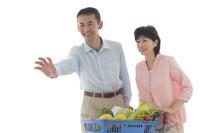 ショッピングカートを押しながら買い物をするシニアの夫婦