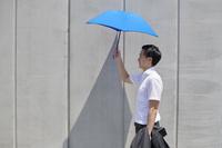 日傘をさす日本人ビジネスマン