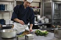 煮魚を皿に盛り付ける調理師