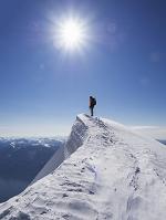 雪山を登山する男性