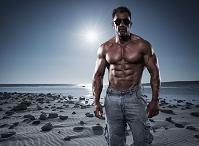 ビーチに立つ筋肉質な外国人男性