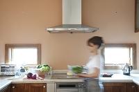 キッチンでサラダを運ぶ女性