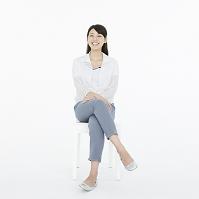 足を組んで椅子に座る日本人女性