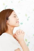 手を組んで祈る日本人女性