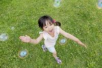 公園でシャボン玉で遊ぶ日本人の女の子
