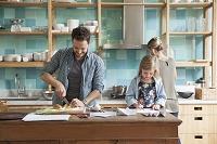 キッチンで調理する外国人男性と女の子